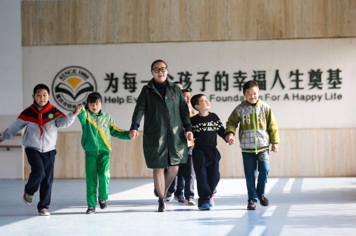 李龙梅和孩子们手牵手走在一起.jpg