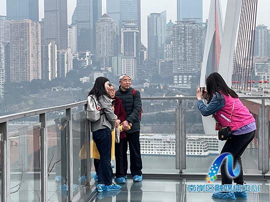 身着红马甲的巾帼志愿者正在为市民游客提供景点拍照服务。(区妇联供图).jpg