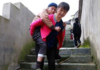 吕正芳背婆婆下阶梯。图片来源:湖南文明网-通讯员-彭伟摄.jpg