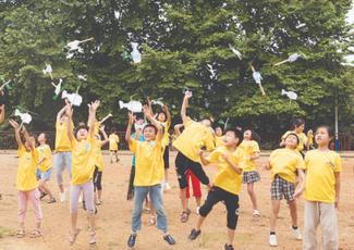 志愿者带孩子们在操场放飞纸飞机。图片来源:株洲新闻网.png