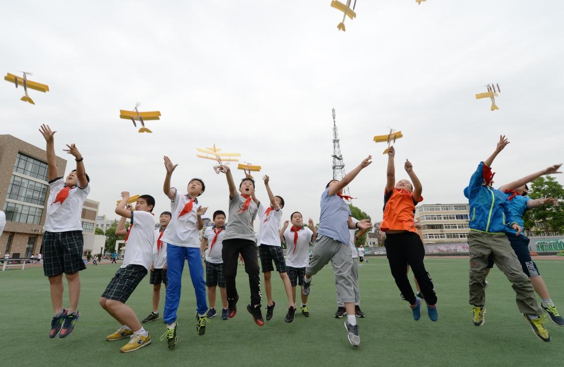 """在波音公司""""放飞梦想——波音航空科普教育项目""""公益活动上,波音少年航校北京延庆二小的学生们放飞亲手制作的航模。新华社记者 李贺 摄"""