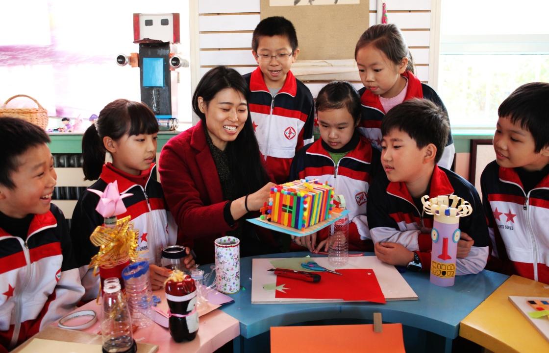 小学老师在指导小学生用废旧物品制作工艺品.新华社记者 王晓 摄-