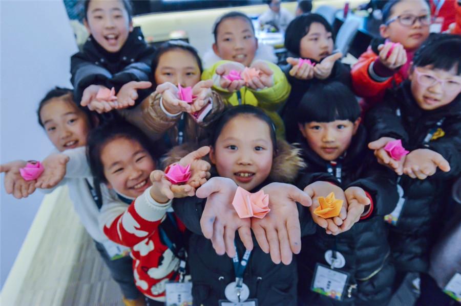 小学生在展示自己折的纸花