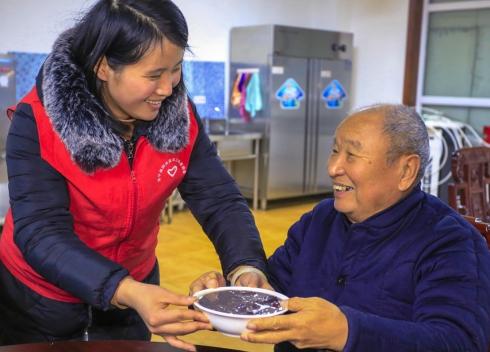 1月13日,一名志愿者为老人端上腊八粥。.jpg
