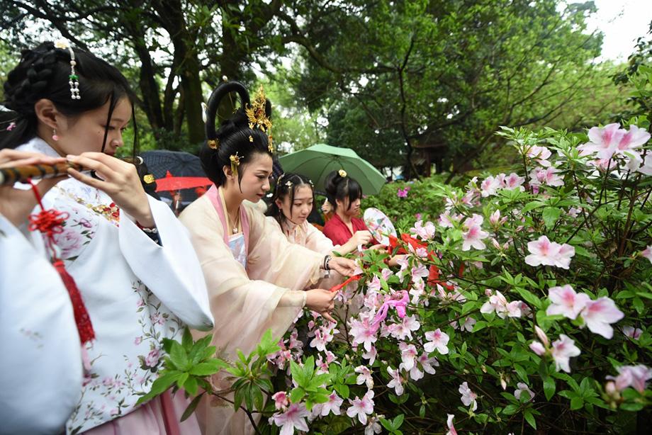 在福州西湖公园,参加花朝节的女士们在扎彩带。新华社记者 林善传 摄   3月20日,是农历二月十二,又逢春分节气。由福建汉服天下、福州西湖公园管理处联合主办的丙申年花朝节传统节俗文化活动在福州西湖举行。身着汉服的女士们表演祭花神祈福,并与游园赏花的群众举行抽花签、香艺等传统艺术展演活动。