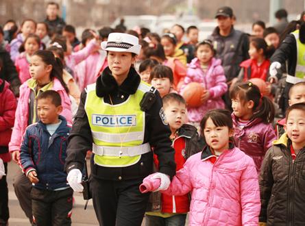 封艳红拉着孩子们的手,护送孩子们安全通过马路。.jpg